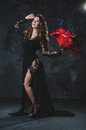Attractive young woman in a long black dress with a very big rose on a grunge wall background Royalty Free Stock Photo