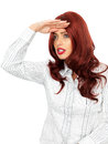 Attractive young woman with long red hair looking into the distance in her twenties a hand raised to her forehead as if searching Royalty Free Stock Image