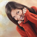 Attractive young woman with a lovely smile wearing soft luxurious wool jersey snuggling into the polo neck for warmth Royalty Free Stock Image