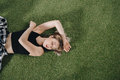 Attractive young woman lying on green grass and looking away Royalty Free Stock Photo