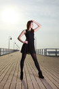 Attractive young woman on the pier full length posing in morning Royalty Free Stock Photo