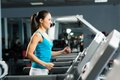 Attractive young woman runs on a treadmill Royalty Free Stock Photography