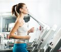 Attractive young woman runs on a treadmill is engaged in fitness sport club Royalty Free Stock Photos