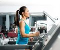 Attractive young woman runs on a treadmill is engaged in fitness sport club Royalty Free Stock Photo