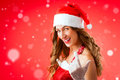 Attractive young woman in santa claus costume alluring gesture snow flakes on isolated red background xmas celebration festive Royalty Free Stock Photography