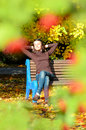 Attractive young woman sitting on brown wooden bench with hands behind her head in beautiful park. She closed eyes Royalty Free Stock Photo