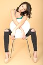 Attractive young woman sitting on a chair in high heel shoes and dslr royalty free image of an with dark brown hair white looking Royalty Free Stock Photography
