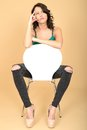 Attractive young woman sitting on a chair in high heel shoes and dslr royalty free image of an with dark brown hair white looking Stock Photography