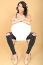 Attractive young woman sitting on a chair in high heel shoes dslr royalty free image of an with dark brown hair white looking Royalty Free Stock Photography
