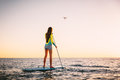 Attractive young woman Stand Up Paddle Surfing and drone copter with beautiful sunset colors Royalty Free Stock Photo