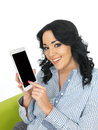 Attractive young woman using a tablet with long black curly hair and hispanic or european features looking at camera smiling Royalty Free Stock Photos