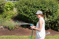 Attractive young woman watering the plants in the garden Stock Photo