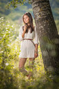 Attractive young woman in white short dress posing near a tree in a sunny summer day beautiful girl enjoying the nature green Stock Photo