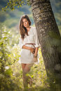 Attractive young woman in white short dress posing near a tree in a sunny summer day. Beautiful girl enjoying the nature Royalty Free Stock Photo