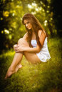 Attractive young woman in white short dress sitting on grass in a sunny summer day. Beautiful girl enjoying the nature