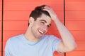 Attraktiver junger mann der mit der hand im haar lächelt Stockfotografie