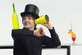 Attributes of good barman half length portrait handsome smiling wearing black topper holding empty yellow bottle on his hand and Royalty Free Stock Images
