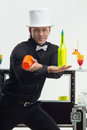 Attributes of good barman handsome wearing nice white topper and bow tie holding in his crossing hands yellow bottle and orange Royalty Free Stock Images