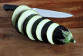 Aubergine slices and knife on wooden board Royalty Free Stock Photos