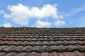 Auburn tiled roof and blue sky with white clouds Stock Image