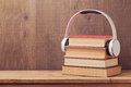 Audio books concept with stack of old book and headphones on wooden table Royalty Free Stock Photo