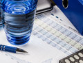 Auditing and calculating finances blue concept with wrapper and graphs close up of financial economic charts glass water Stock Images