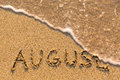 August - word drawn on the sand beach with the soft wave. Royalty Free Stock Photo