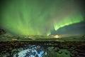 Aurora Borealis in Tromso, Norway in front of Norwegian fjord at winter