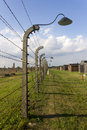 Auschwitz II -Birkenau Extermination camp barbed wire fence and wooden housing Royalty Free Stock Photo