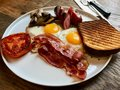 Aussie / Australian Breakfast with Brioche Toast, Fried Eggs, Crispy Bacon Sausage, Salty Pancakes and Mushrooms Royalty Free Stock Photo