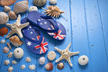 Australia travel shells background a blue painted rustic wood with australian flag thongs starfish and Royalty Free Stock Photography
