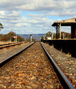 Australian country railroad and station railway deserted train with traintracks crossing with clouds in sky Stock Image