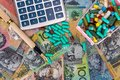 stock image of  Australian dollars with cart full of pills, pen and calculator