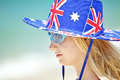 Australian girl beach a young with flag hat and glasses at the Royalty Free Stock Photos