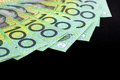 Australian one hundred dollar bills fanned over black background Stock Photo