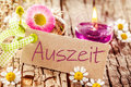 Auszeit or time out for relaxation decorative background with a burning aromatherapy candle and pretty summer flowers on old Royalty Free Stock Images