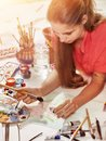 Authentic artist children girl paints on floor. Sun flare. Royalty Free Stock Photo