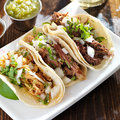 Authentic mexican barbacoa carnitas and chicken tacos close up photo of three Royalty Free Stock Images