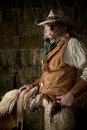 Authentic western cowboy with leather vest, cowboy hat and scarf portrait Royalty Free Stock Photo