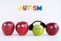 Autism apple series four apples are lined up in a row of the apples are red an is green the green is wearing headphones indicating Stock Photo