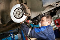 Auto mechanic at car suspension repair work examining of lifted automobile service station Stock Image