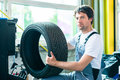 Auto mechanic changing tire in workshop Royalty Free Stock Photo