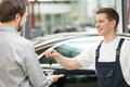 Auto mechanic and customer cheerful giving a car key to smiling Royalty Free Stock Image