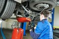 Auto mechanic disassembling axle repairman works with rear reduction gear of commercial van in car repair or maintenance shop Stock Image