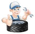 Auto mechanic giving thumbs up with a spanner and mobile vehicle tyre Stock Images