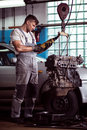 Auto mechanic inspecting motor car Royalty Free Stock Photo