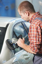 Auto mechanic polishing car body worker at automobile repair and renew service station shop by power buffer machine Stock Photos
