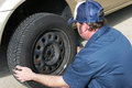 Auto mechanic removing the tire from a car Royalty Free Stock Image