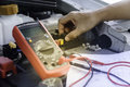 Auto mechanic uses a multimeter voltmeter. Royalty Free Stock Photo
