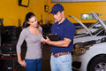 Auto mechanic woman and young women customer in workshop Royalty Free Stock Photo